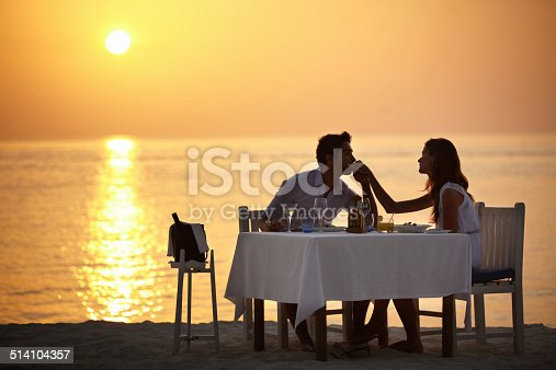 A young man kissing the hand of his wife while having dinner on the beach