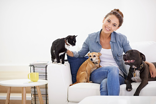 Shot of a beautiful young woman relaxing on the couch with her pets