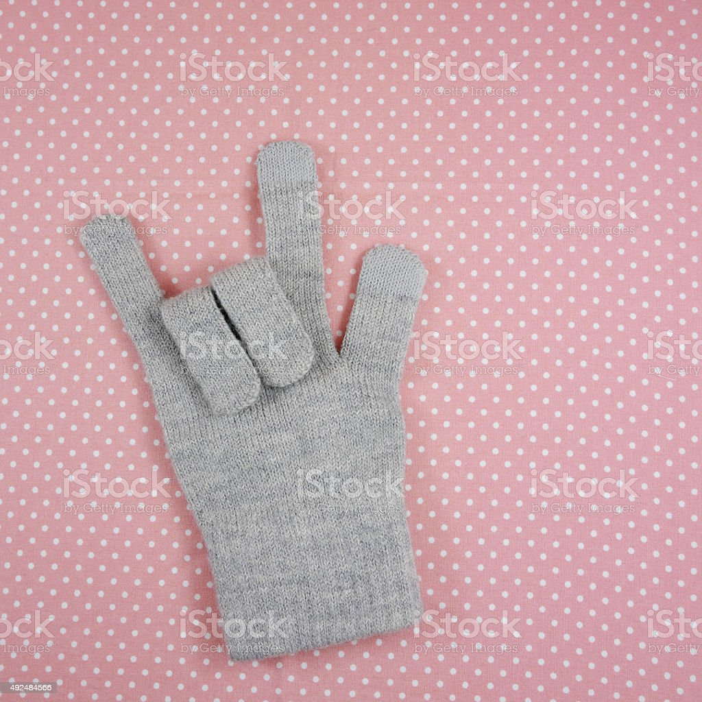 The love sign showing by knitted grey glove stock photo