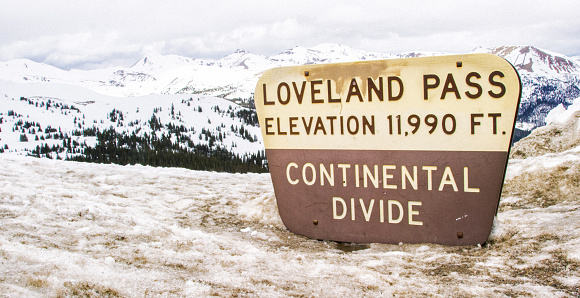 """The """"Loveland Pass: Elevation 11,990 Ft. Continental Divide"""" Sign at the Top of Loveland Pass with the Snowcapped Rocky Mountains of Colorado in the Background under an Overcast Sky in Winter"""