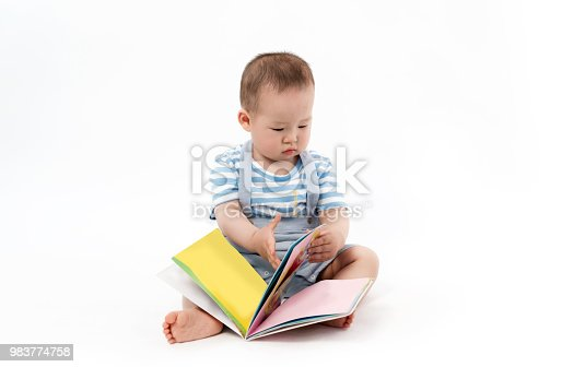 istock The lovely baby is reading a Book in the white background 983774758