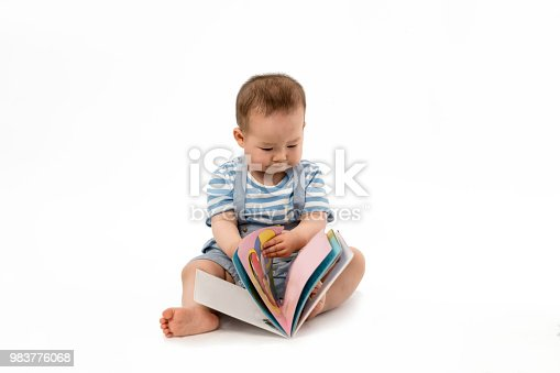 istock The lovely baby is reading a Book in the white background 983776068