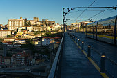 Porto, Portugal - December 02, 2019: The Luis I bridge at sunrise with the trams crossing and view of Porto city reflected in the windows.