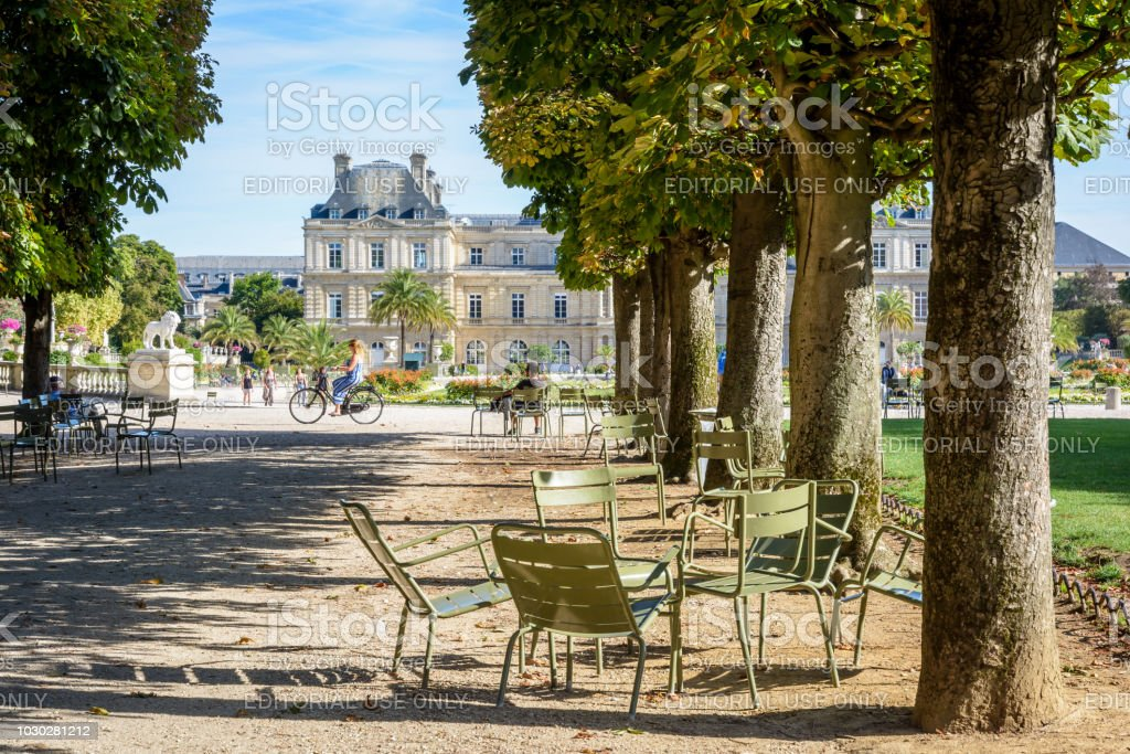 The Luxembourg garden in Paris, France, by a sunny summer morning with the Luxembourg palace in the background. Paris, France - August 12, 2018: The Luxembourg garden is greatly prized by parisians and tourists for its shady tree lined alleys, its metal lawn chairs and its view over the Luxembourg palace. Alley Stock Photo