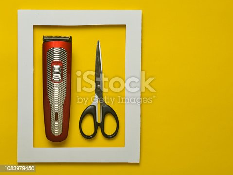 1147090180 istock photo The machine for a hairstyle and scissors in a white frame on a yellow background. Minimalist trend. Copy space. 1083979450