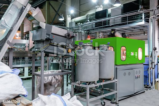 istock The machine for blowing plastic PET bottles 645642048