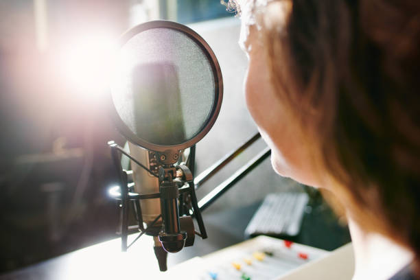 The magic happens behind the mic Shot of a woman speaking into a microphone in a recording studio radio dj stock pictures, royalty-free photos & images