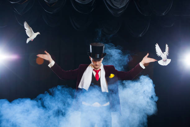 The magician with a two flying white Doves. on a black background shrouded in a beautiful mysterious smoke stock photo