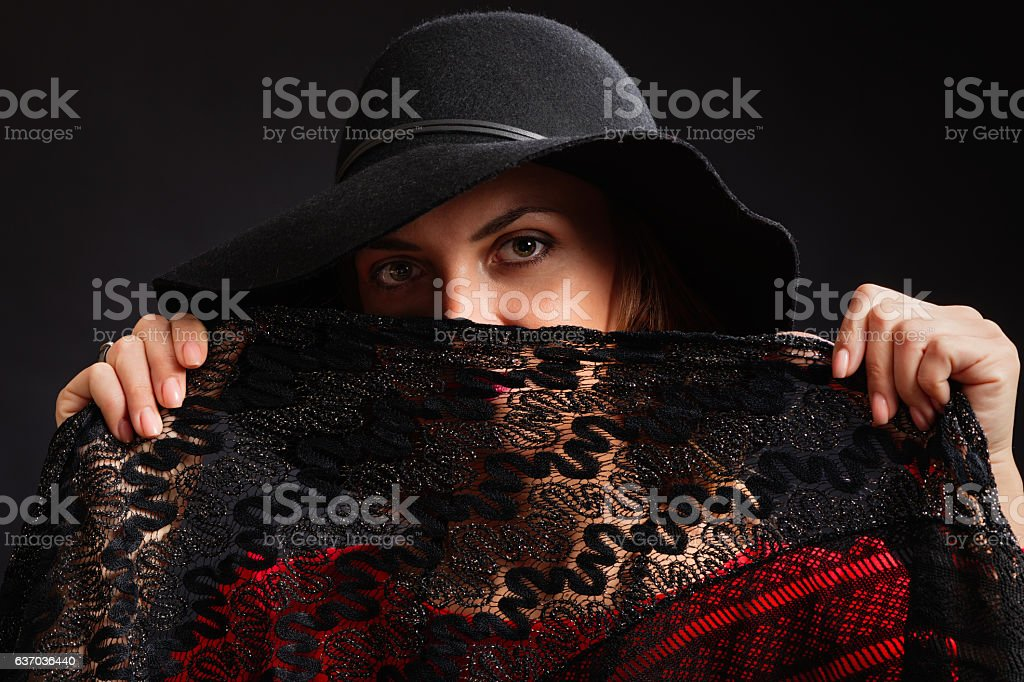 The magnificent beautiful woman in a black wide-brimmed hat стоковое фото