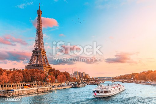istock The main attraction of Paris and all of Europe is the Eiffel tower in the rays of the setting sun on the bank of Seine river with cruise tourist ships 1185953092