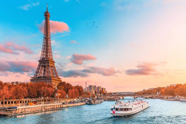 główną atrakcją paryża i całej europy jest wieża eiffla w promieniach zachodzącego słońca nad brzegiem sekwany z rejsami turystycznymi - francja zdjęcia i obrazy z banku zdjęć
