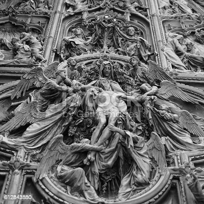 a bottom view of the main door of Milan Cathedral
