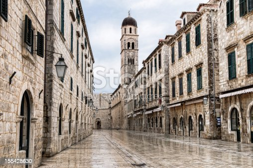Looking down the main street of the old town of Dubrovnik, Croatia.  The street is empty because it is very early in the morning and there is a light rain which makes the cobble stones glisten.