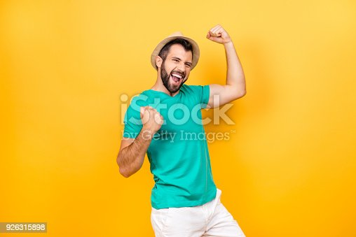 istock The main task is completed! Yeah! I did it! I reached so long desired success! Happy excited cheerful joyous guy celebrating his victory with raised hands, isolated on yellow background 926315898