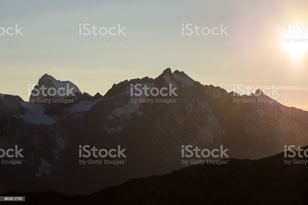 The majestic peaks of the Massif des Ecrins (4101 m) national park with the glaciers, in France. Telephoto view from distant at sunrise. Clear sky, autumn colors. stock photo