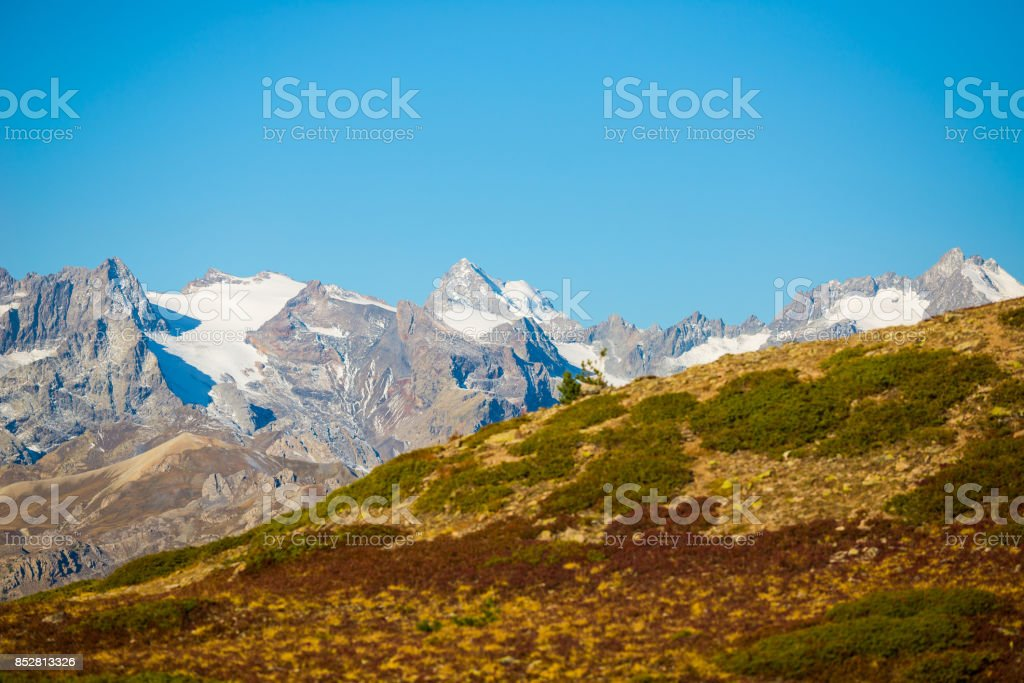 The majestic peaks of the Massif des Ecrins (4101 m) national park with the glaciers, in France. Telephoto view from distant at high altitude. Clear sky, autumn colors stock photo