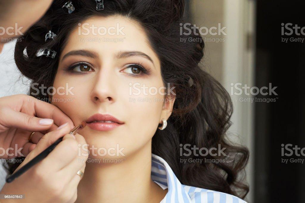 Make-up artist gör en makeup för bruden. Makeupartist gäller rött läppstift. Vacker kvinna ansikte. Hand av make-up master, målning läppar av unga skönhet modell flicka. Göra upp i processen - Royaltyfri Applicera Bildbanksbilder