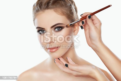 istock The make-up artist paints eyebrows  and eyes to a beautiful girl. 1061793784