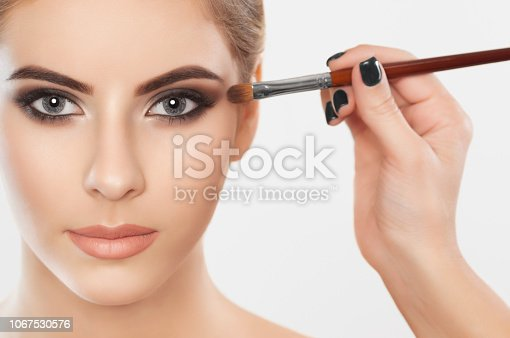 istock The make-up artist paints eyebrows  and eyes to a beautiful girl. 1067530576