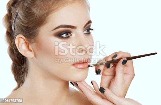 istock The make-up artist paints the lips of a beautiful woman,  completes the day's make-up in the beauty salon 1061793756