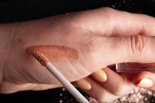 메이크업 아티스트는 모델의 얼굴에 적용 하기 전에 리퀴드 립스틱의 색상을 테스트 하 고 선택 합니다. 스톡 사진