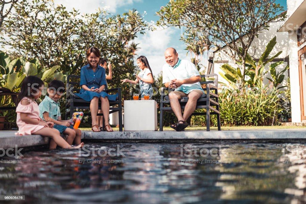 Die malaysische Familie genießen den Pool an einem schönen sonnigen Tag – Foto