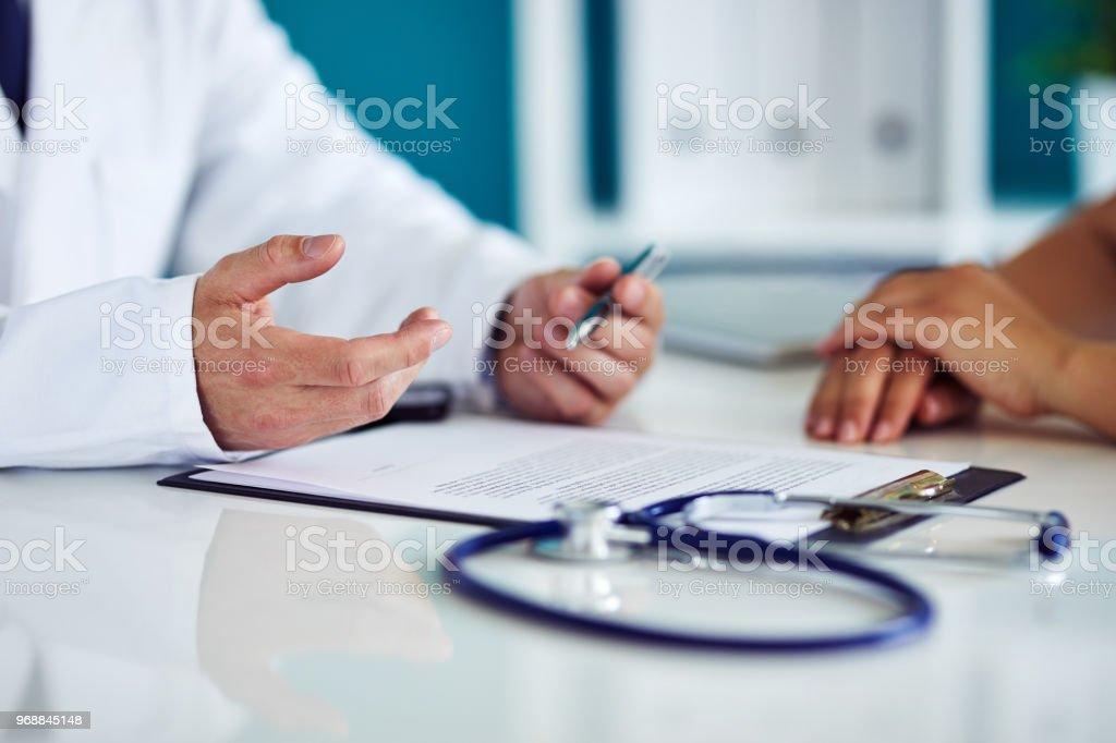 Der männlichen Arzt im Büro hat mit seinem Patienten konsultiert. – Foto