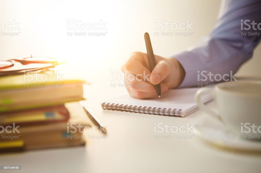 The male hand with a pen and the cup stock photo
