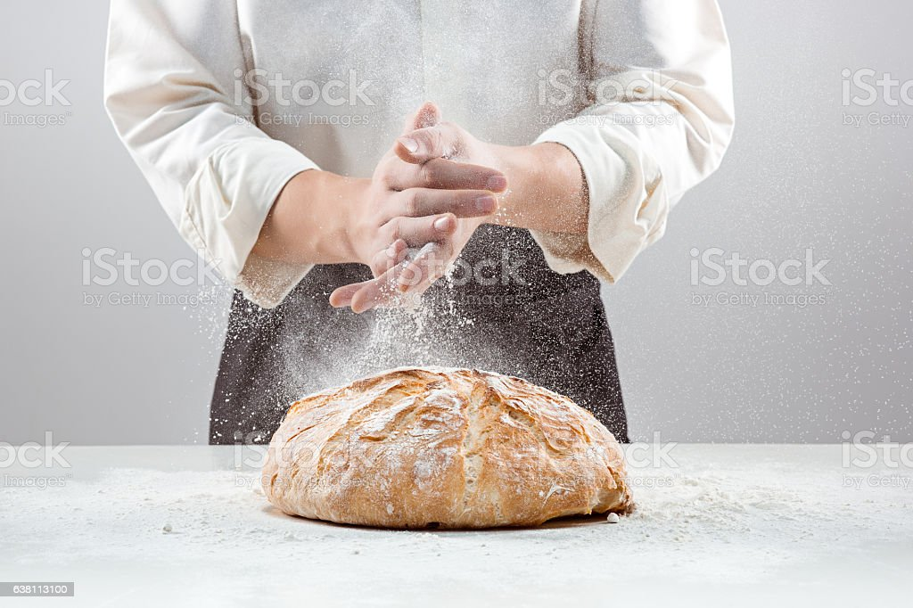 The male hands in flour and rustic organic loaf of - Photo