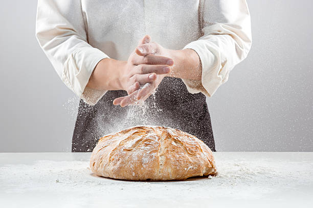 the male hands in flour and rustic organic loaf of - boulanger photos et images de collection