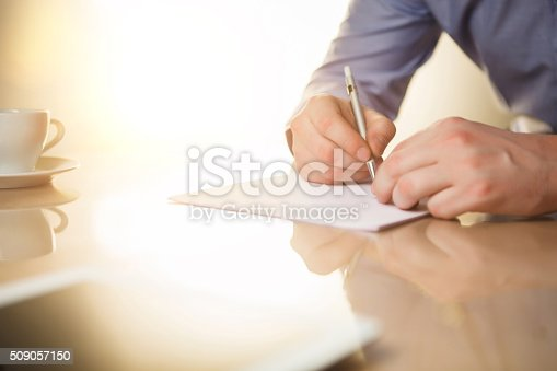 istock The male hands with a pen and the cup 509057150