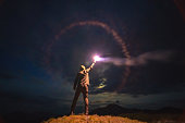 The male with a bright firework stick standing on a mountain. evening night time