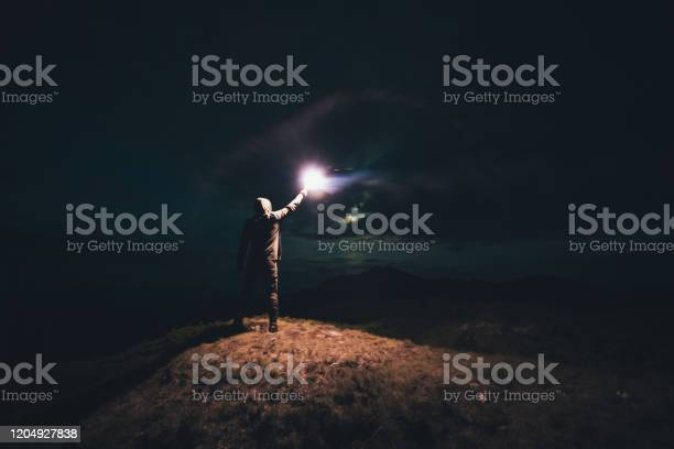 Photo of The male with a bright firework stick standing on the night mountain