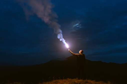 The male with a firework stick standing on a mountain