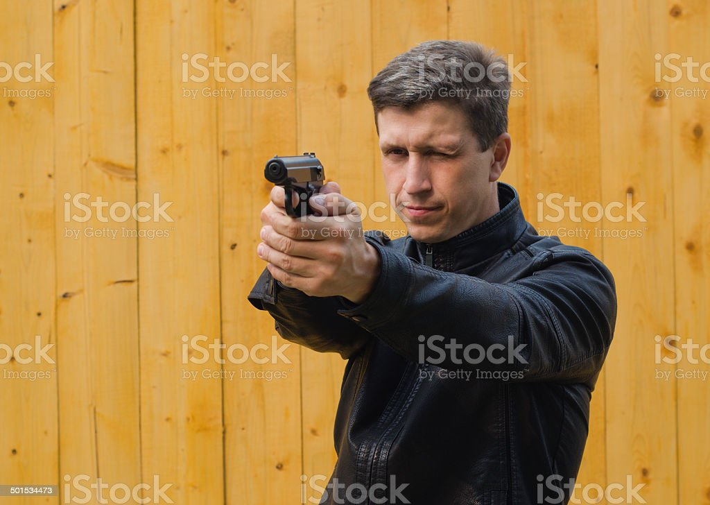 The man  aims from a pistol stock photo