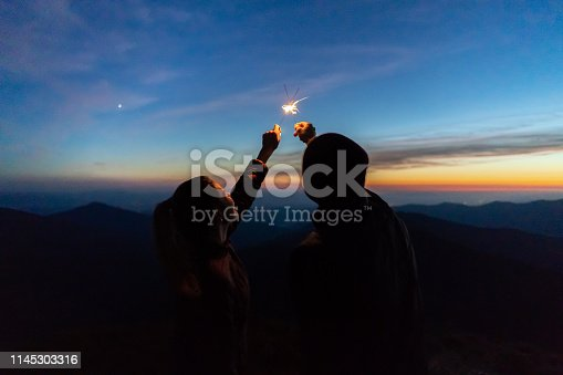 The man and a woman hold firework sticks. evening night time