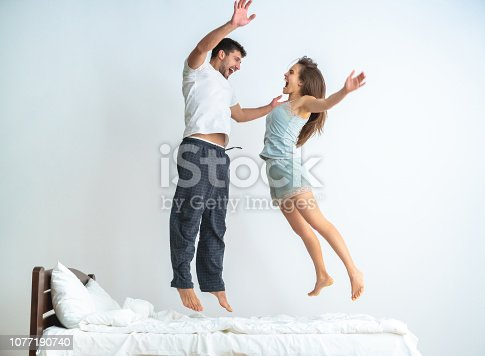 504371332 istock photo The man and a woman jumping on the bed on the white background 1077190740