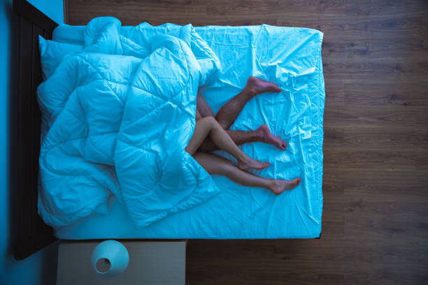 The man and a woman laying under a duvet. evening night time. view from above The man and a woman laying under a duvet. evening night time. view from above couple in bed stock pictures, royalty-free photos & images