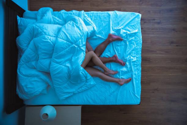 der mann und eine frau, die unter einer bettdecke lag. abendliche nacht. blick von oben - sex sexuelle themen stock-fotos und bilder