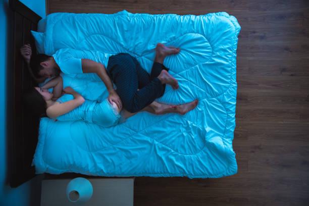der mann und eine frau auf dem bett schlafen. am abend, nacht, ansicht von oben - nachttischleuchte touch stock-fotos und bilder