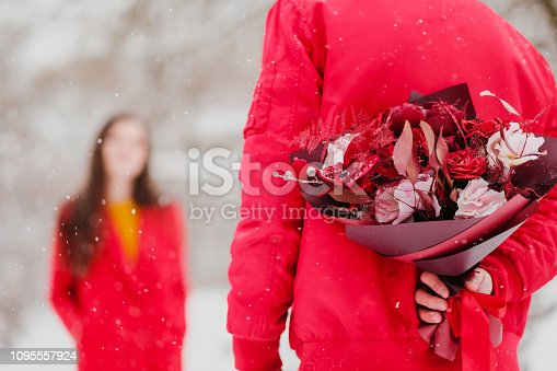 istock The man and the woman meet in snow-covered park in the winter. The guy is hiding behind a bouquet of flowers, a surprise for the girl. 1095557924