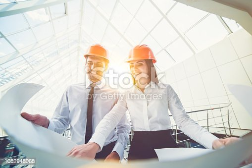 istock The man and woman in a helmets hold the project plan in the building 1082948068