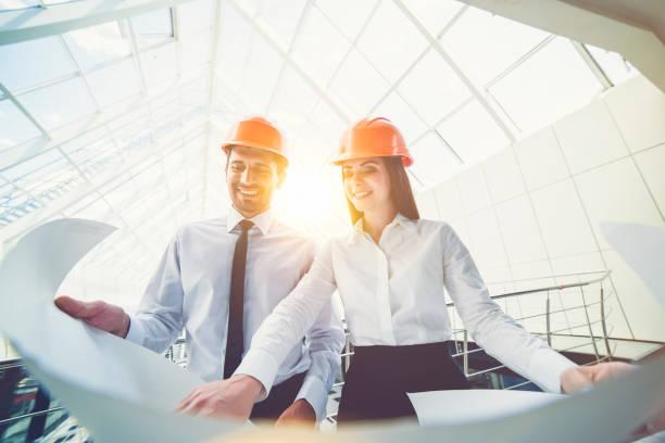 el hombre y la mujer en un casco mantenga el plan del proyecto en el edificio - ingeniero fotografías e imágenes de stock