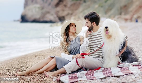 The man and woman in love. Two young lovers cuddle and kiss on the beach.