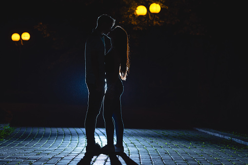 The man and woman kissing on the dark alley. night time