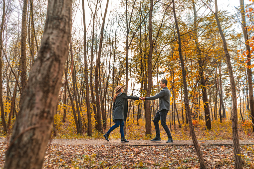 The man and woman playing in the autumn park