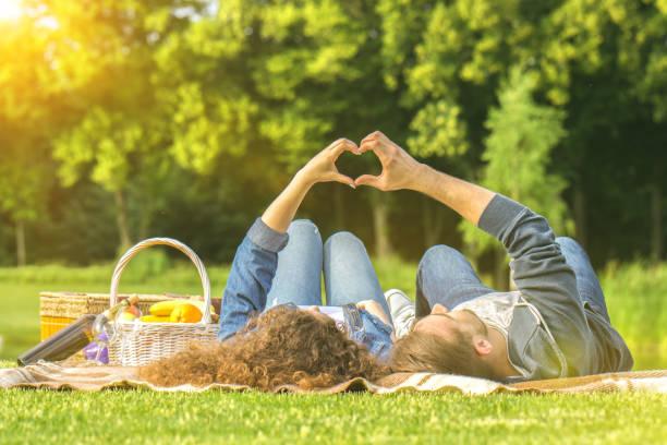 der mann und die frau im park ausruhen und zeigen sie ein herz zeichen - romantisches picknick stock-fotos und bilder
