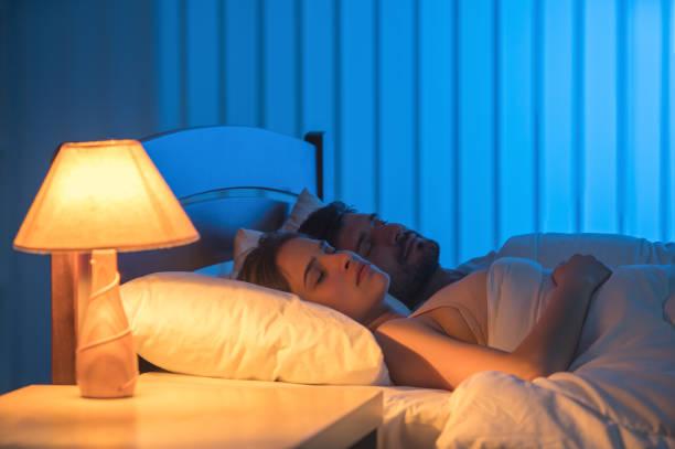 der mann und die frau schliefen im bett. nachtzeit, voller grifffokussierung - nachttischleuchte touch stock-fotos und bilder