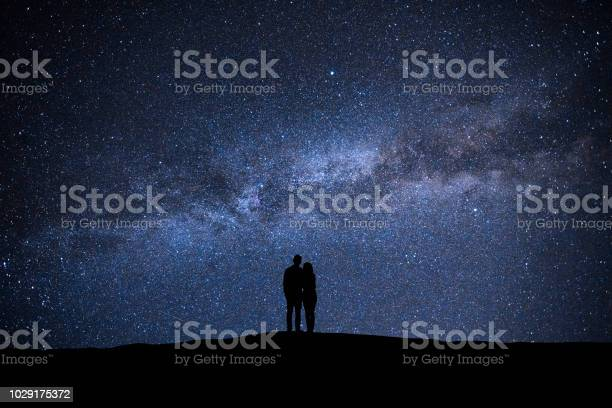 Photo of The man and woman standing on the sky with stars background