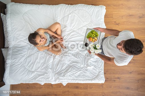 504371332 istock photo The man bringing a breakfast for a woman on the bed. view from above 1077173744